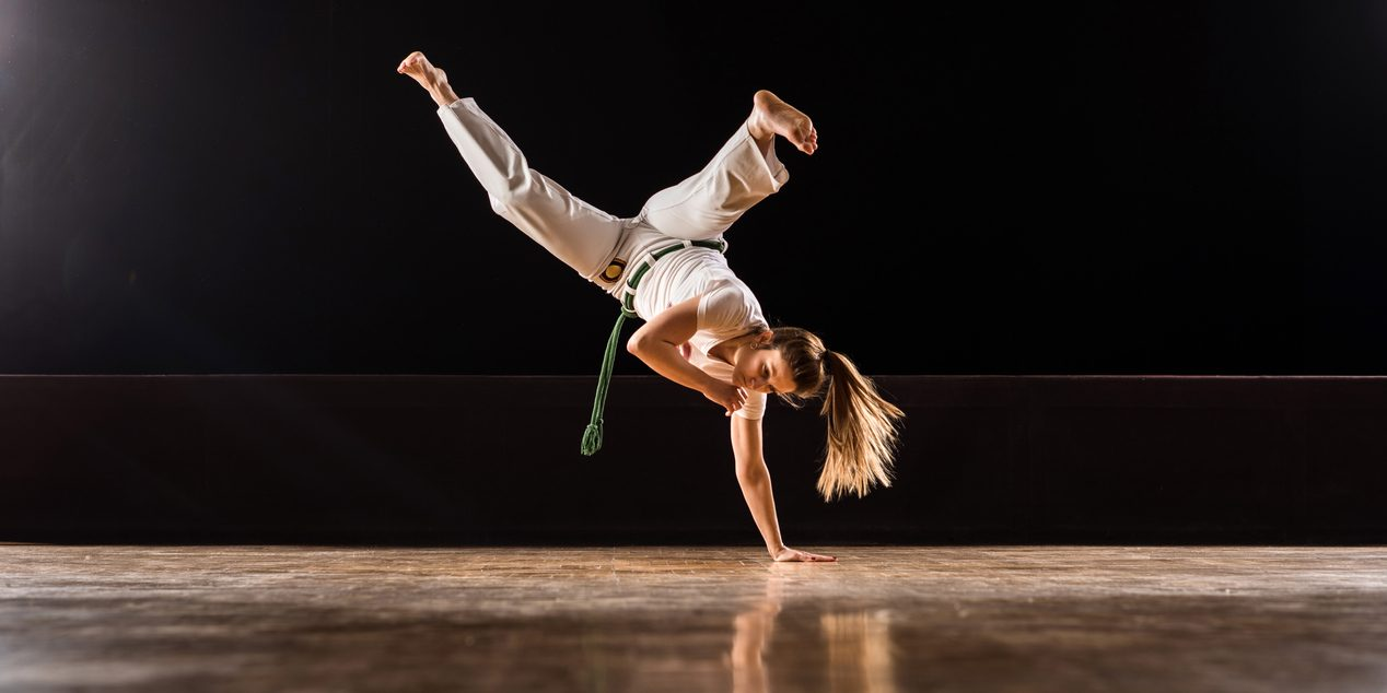 Capoeira female athlete doing a handstand on sports training in a health club. Copy space.