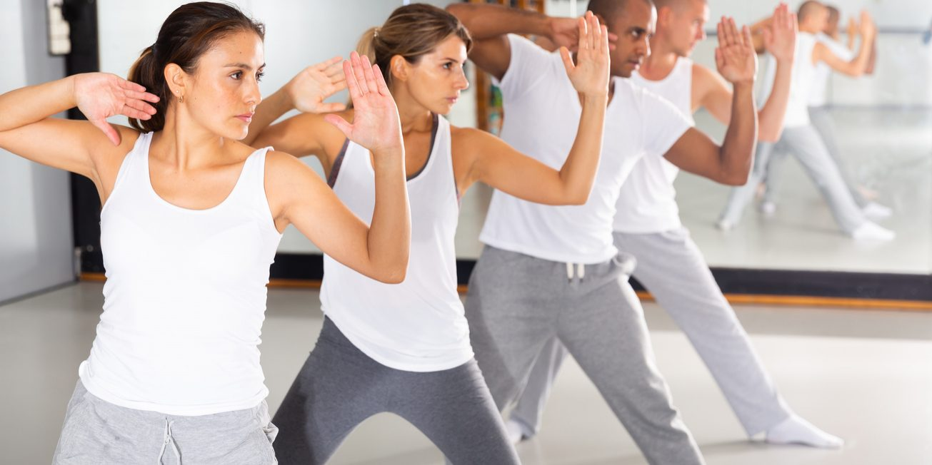 Group of beginners mastering martial arts for self defence, synchronously repeating basic movements in gym